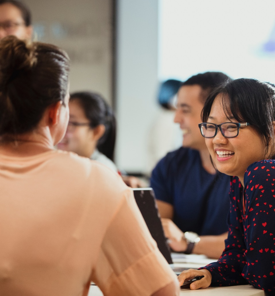 Smiling Asian woman at work with other people